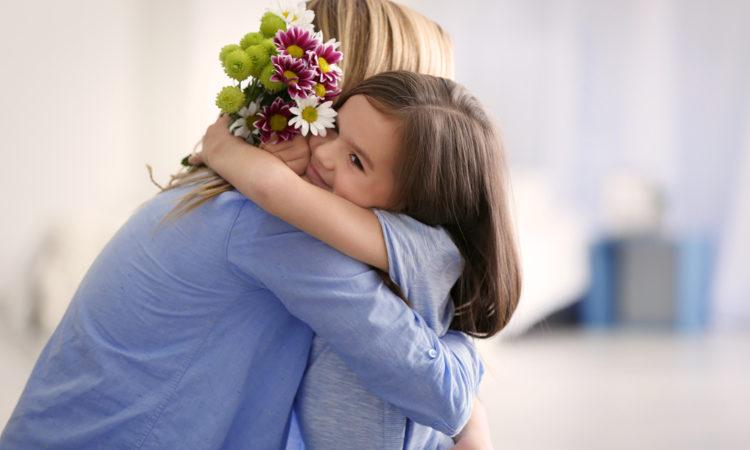 Tochter schenkt Mutter Blumen zum Muttertag